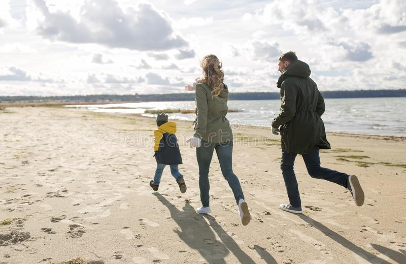 Happy family running along autumn beach royalty free stock photography