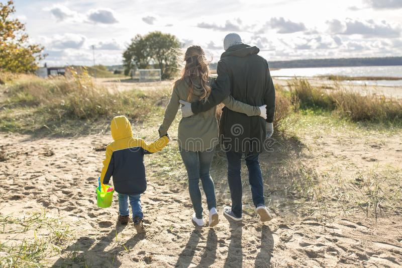Happy family walking along autumn beach stock photography
