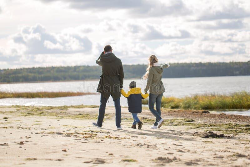 Happy family walking along autumn beach royalty free stock photo