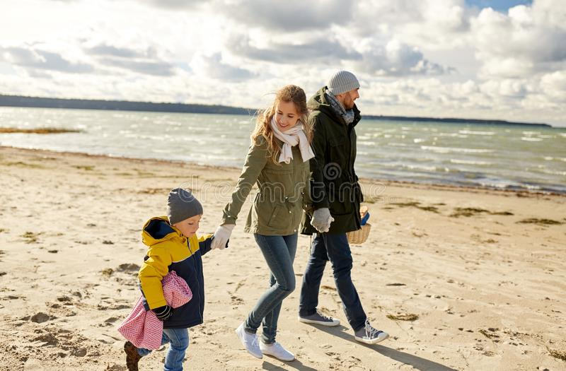 Happy family going to picnic on beach in autumn stock images