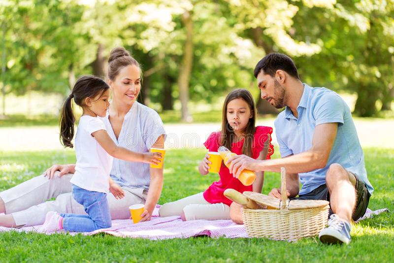 Family drinking juice on picnic at summer park. Family, leisure and people concept - happy mother, father and two daughters having picnic and drinking orange royalty free stock photo