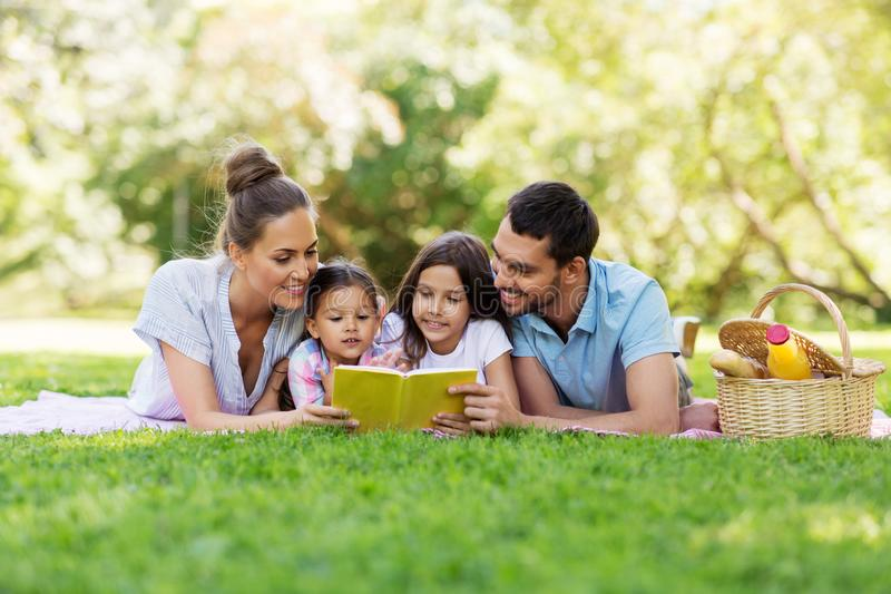 Family reading book on picnic in summer park royalty free stock photography