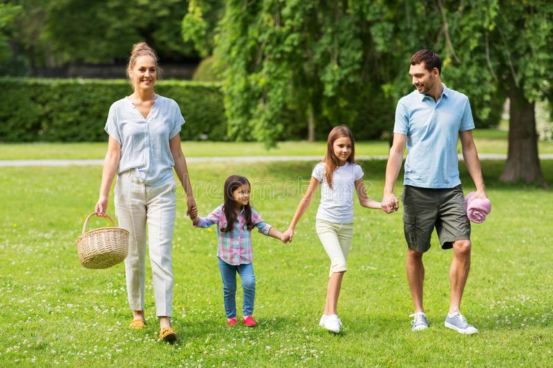 Family with picnic basket walking in summer park stock image