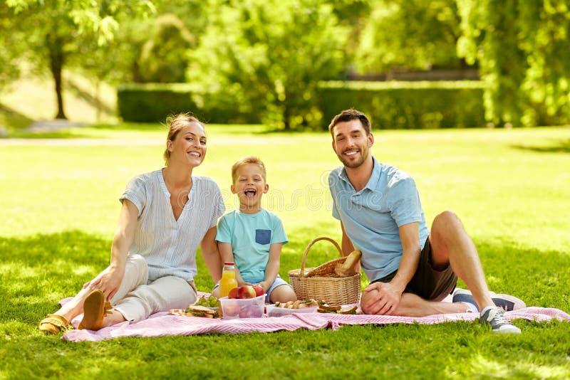 Portrait of family having picnic at summer park stock image