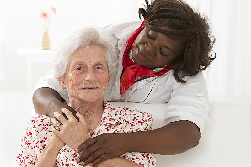 Family life - complicity between a senior woman and her care giver. Happy senior patient with friendly female nurse royalty free stock image