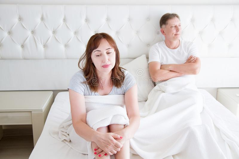 Family life concept.Problems in relationships. Middle age couple in bedroom. Man and woman in bed. Quarrel and upset emotions. stock photography