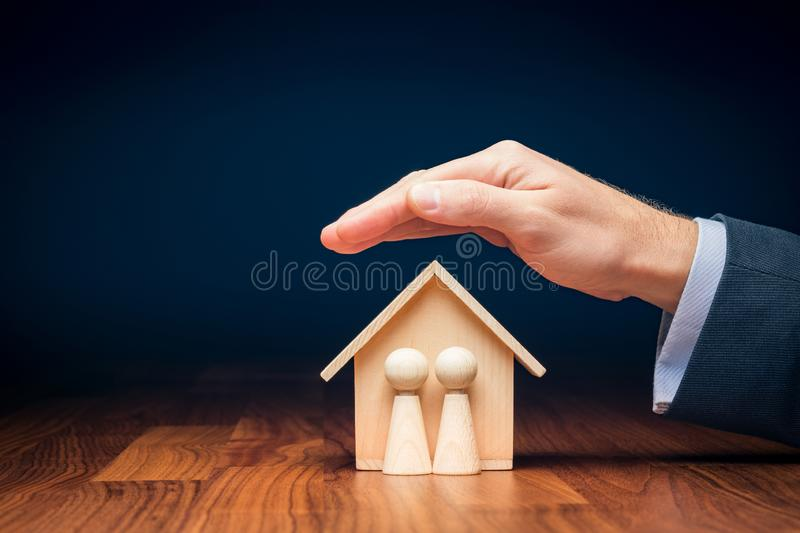 Family life and property insurance concept. Wooden figurines representing family and wooden house and businessman hand with protective gesture, symbol of royalty free stock photography