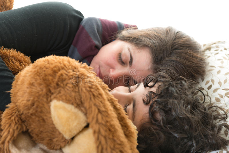 Family life.Single mother sleeping with son. Single mother sleeping with her son and a teddy bear. Candid picture of a small family. Normal life at home stock photos