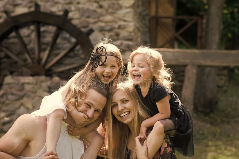 Family life. Summer vacation, adventure, discovery, wanderlust concept. Girls sit on women and men shoulders. Mothers, fathers day. Happy childhood, family royalty free stock photography