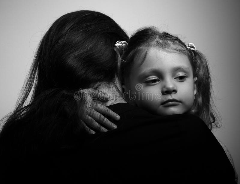 Family lifestyle. Daughter hugging her mother and looking serious stock photos