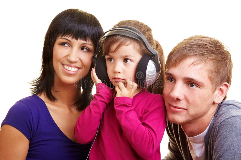 Family listening to music. Girl with headphones listening to music around her parents stock images