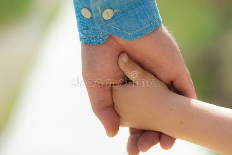 Family. Little child holding hands with his father outdoors, closeup. Family time. Closeup of two touching hands of royalty free stock image