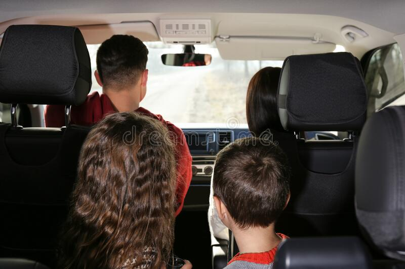 Family with little children inside car stock photography