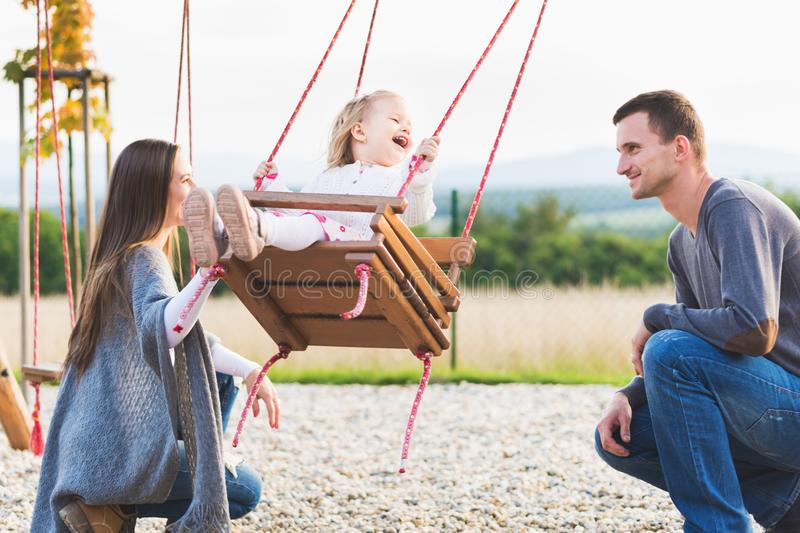 Family with little girl swinging on a playground. Childhood, Family, Happy, Summer Outdoor Concept. royalty free stock photo