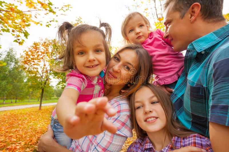 Family with little kids sit, play in autumn park royalty free stock photo