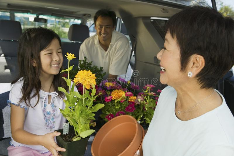 Family loading flowers into SUV royalty free stock photo