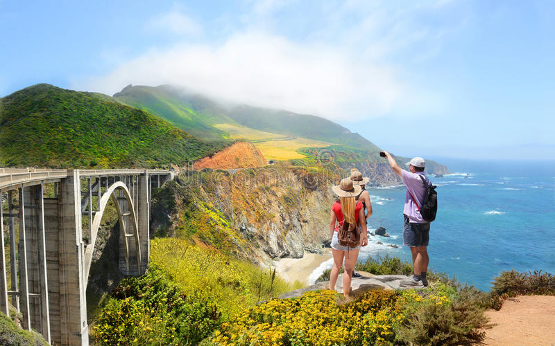 Family relaxing on hiking trip in high mountains. Family looking at beautiful summer mountains landscape, on hiking trip. Father taking photos of Bixby Bridge stock photo