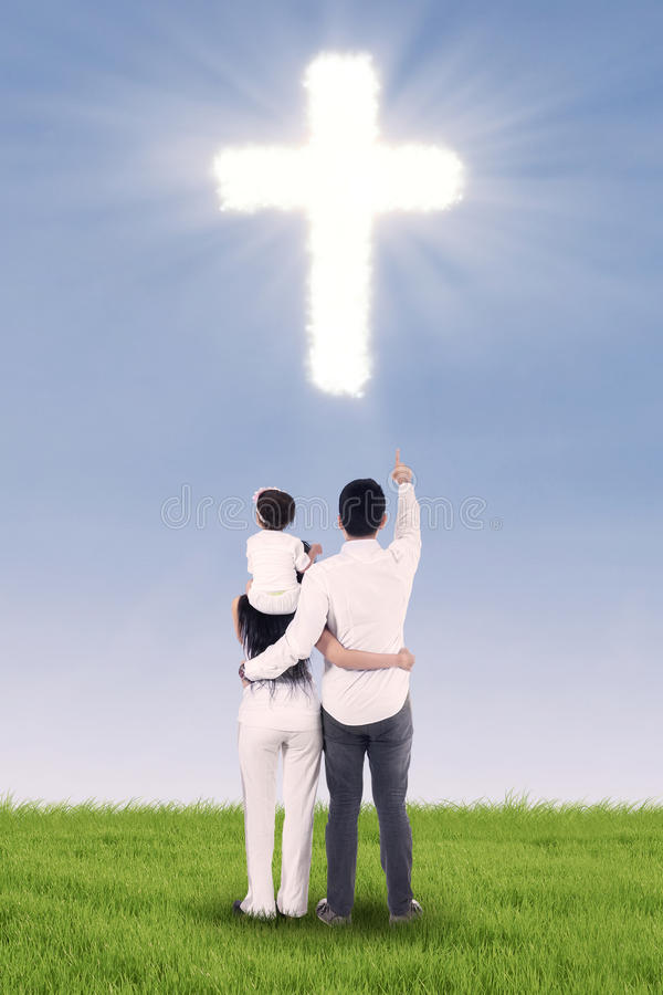 Family looking at bright cross. Christian family looking at bright cross in the park stock photos