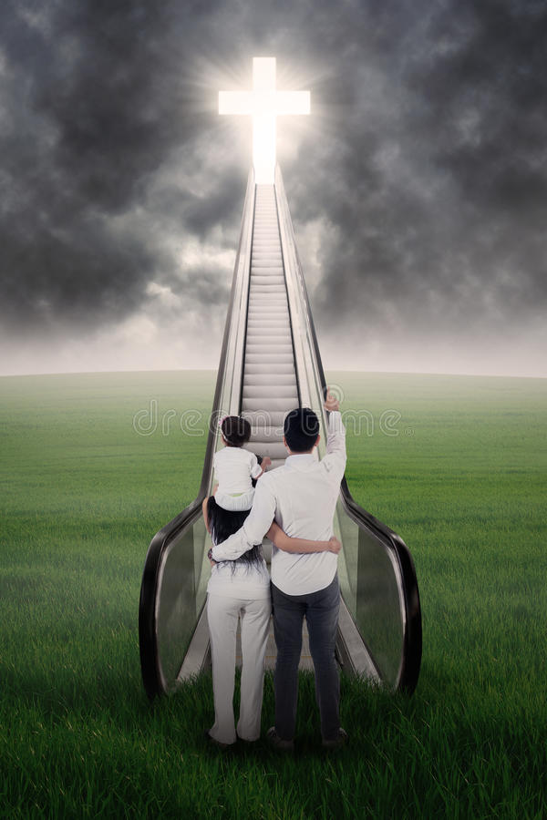 Family looking at cross. Christian family looking at cross under bad weather royalty free stock photo