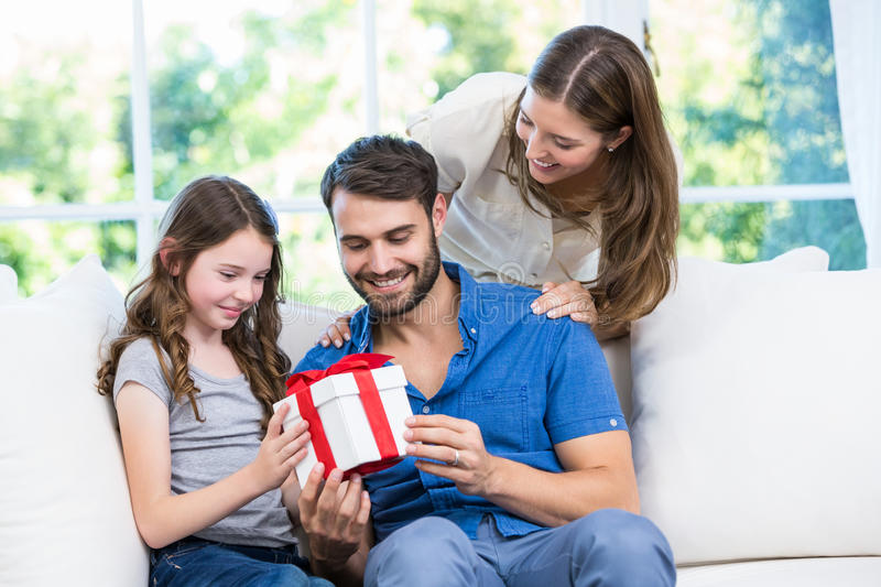 Family looking at gift. In house royalty free stock photos