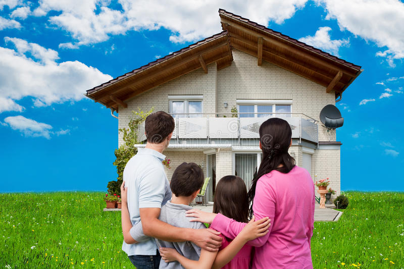 Family Looking At New House On Grassy Field. Rear view of family looking at new house on grassy field against sky royalty free stock images