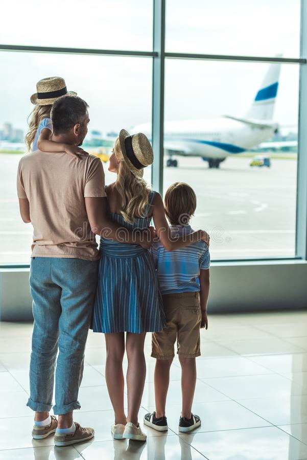 Family looking out window in airport stock photos