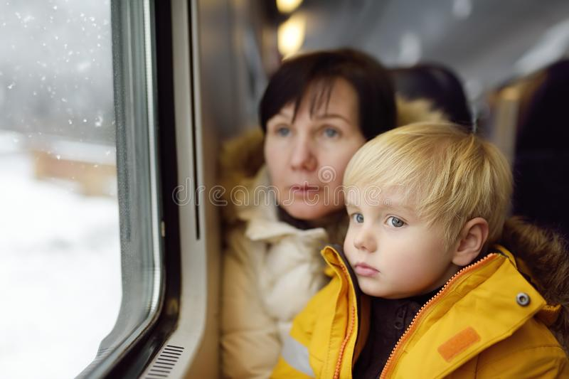 Family looking out of the window of train during travel on cogwheel railway/rack railway in Alps mountains. Winter holidays in Swiss/German/Italian Alps stock photos