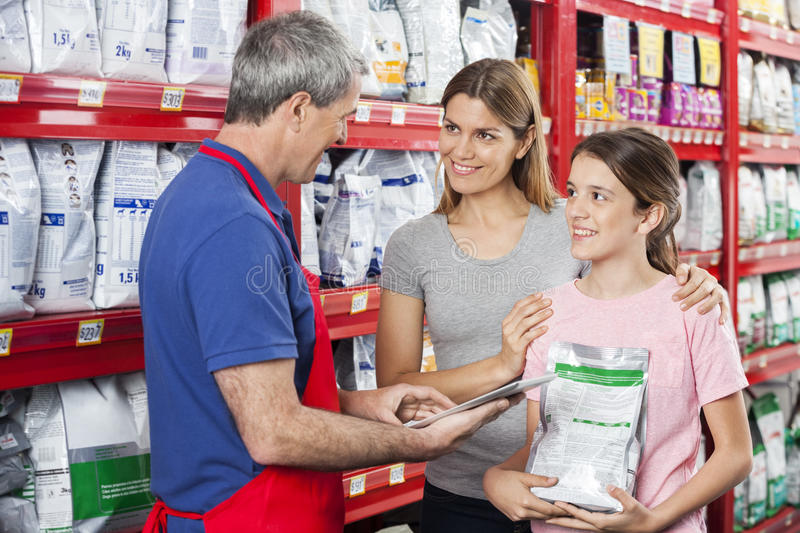 Family Looking At Salesman Using Digital Tablet In Pet Store stock photography