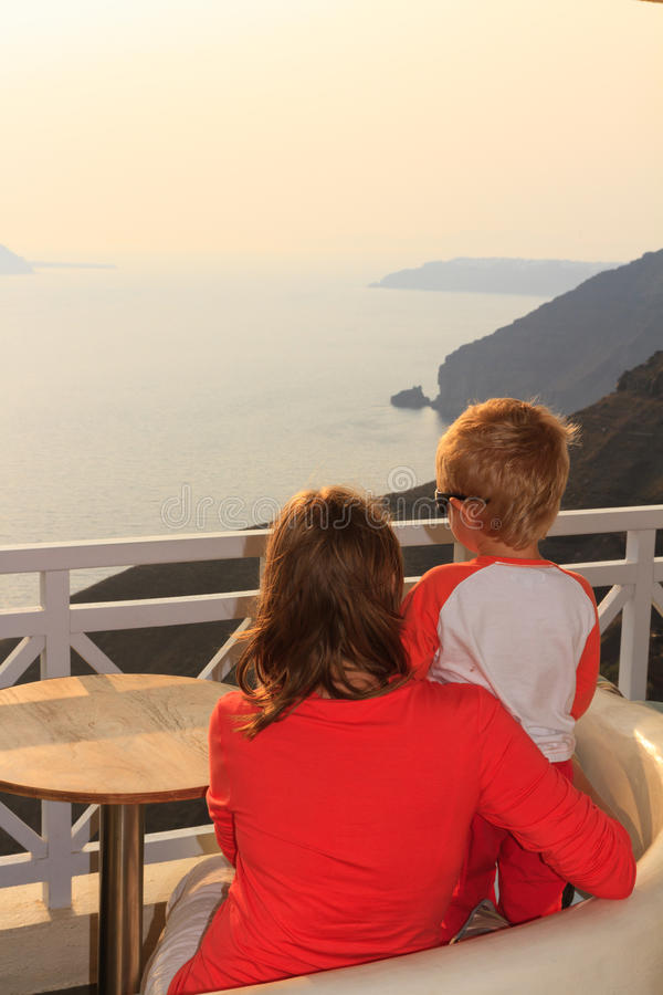 Family looking at sunset Santorini. Mother and son looking at sunset Santorini royalty free stock photography
