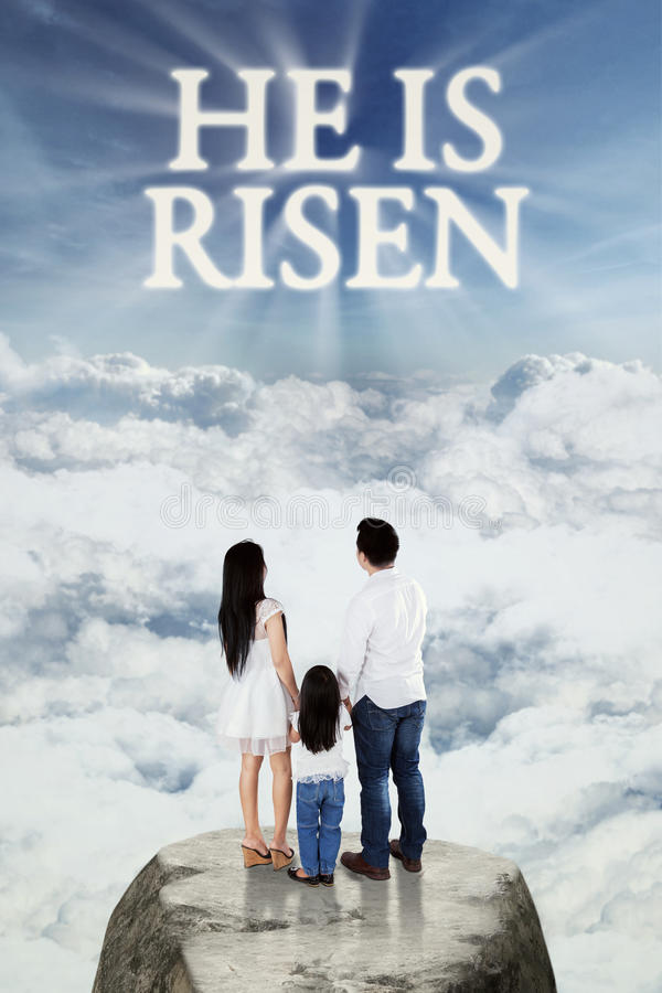 Family looking at text he is risen. Image of two young parents and their daughter standing on the rock and looking at text he is risen on the sky royalty free stock images