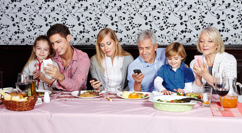 Family looking at their smartphones stock photography