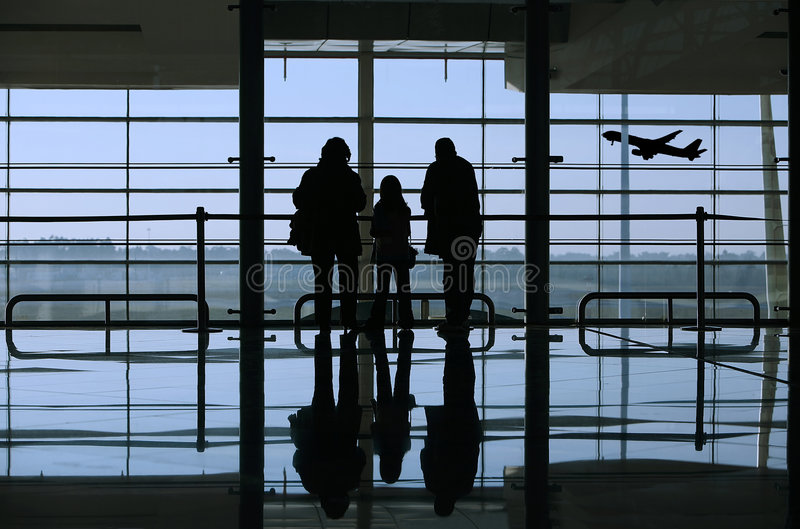 Family looking to an airplane through the window stock image