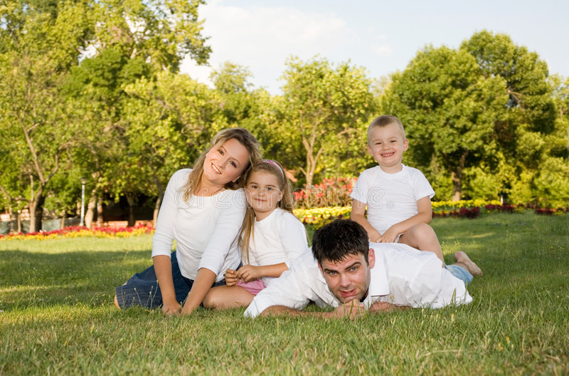 Family love. Young family playing at the park ona a sunny day royalty free stock photo