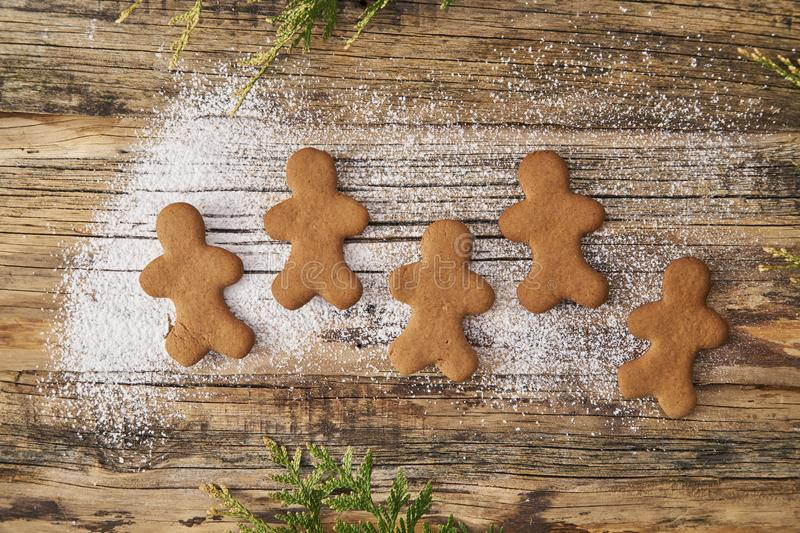 Family love Christmas homemade gingerbread sprinkled with powdered sugar on a wooden background. With spruce needles royalty free stock image