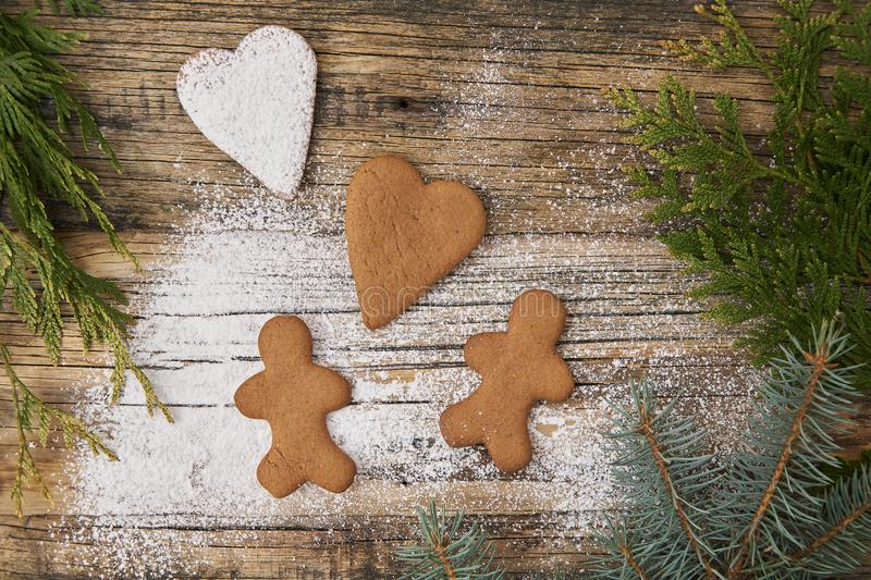 Family love Christmas homemade gingerbread sprinkled with powdered sugar on a wooden background. With spruce needles stock photo