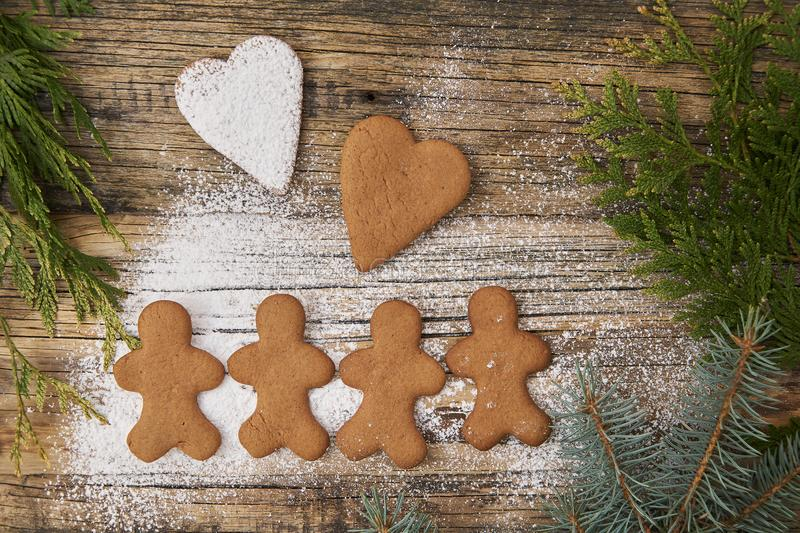 Family love Christmas homemade gingerbread sprinkled with powdered sugar on a wooden background. With spruce needles royalty free stock photo