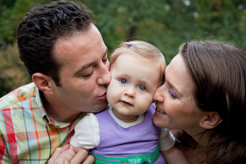 Family love - parents kiss for daughter stock photo