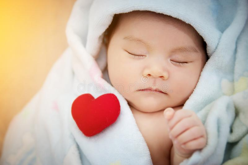 Family love relationship concept : red heart shaped put on sleep. Cute Asian baby. Lovely newborn Asia infant model female in her first year royalty free stock photos