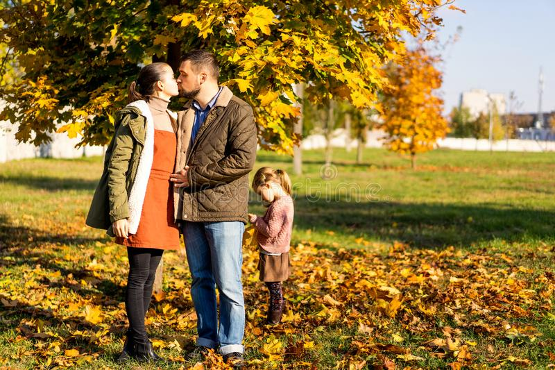 Family in love walks in autumn park stock photography