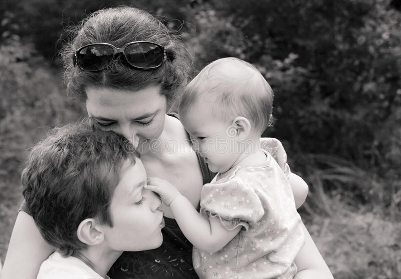 Family in loving embrace. Mother and two children in loving embrace, black and white royalty free stock image