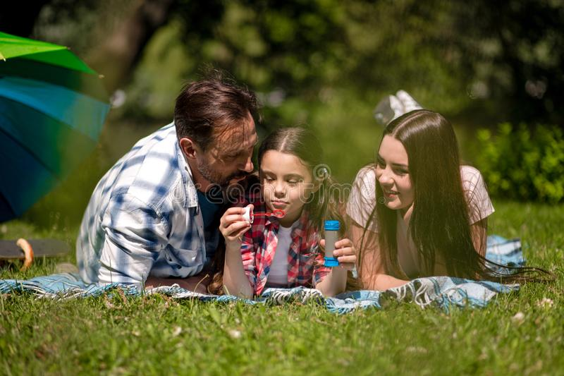 Family Lying On The Blanket In The Park. Daughter Holding Soap Bubbles. stock images