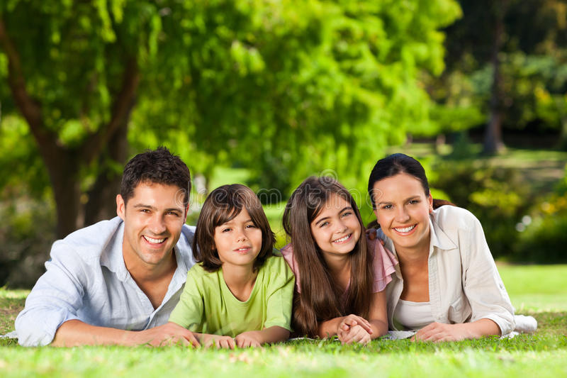Family Lying Down In The Park Stock Image