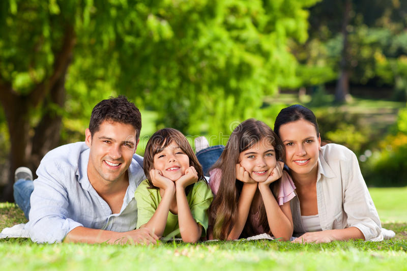 Family lying down in the park royalty free stock images
