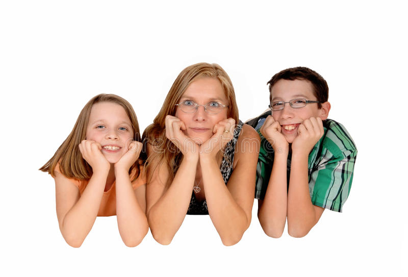 Family lying on floor. A mother with her two kids lying on the stomach on the floor and there faces in there hands, isolated for white background stock photography