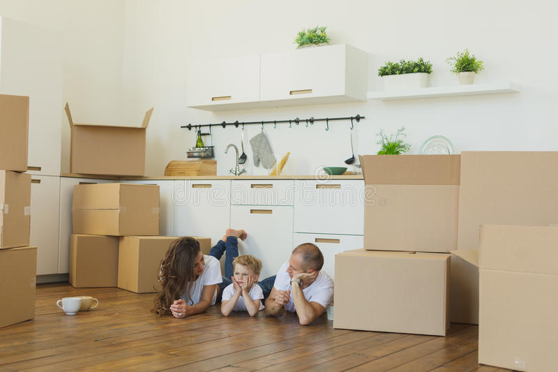 Family lying on floor by open boxes in new home smiling stock image