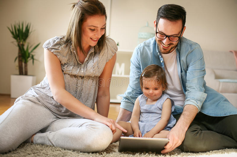 Family lying on the floor with their baby. stock photo