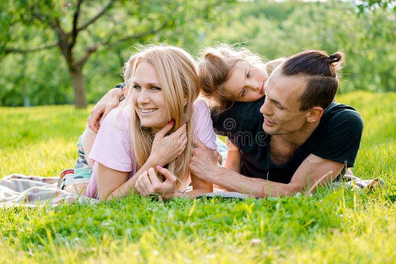 Family lying on grass in countryside stock image