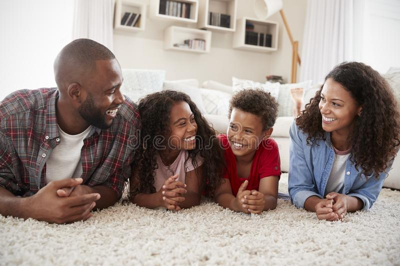 Family Lying On Rug In Lounge At Home stock photo