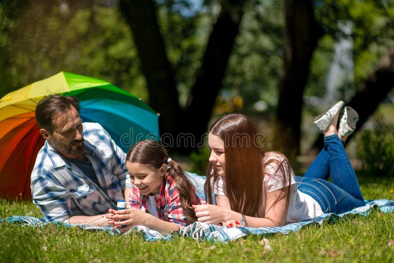 Family Lying Together On A Picnic Blanket Outdoors In The Park. Colorful Umbrella On The Background. stock photography