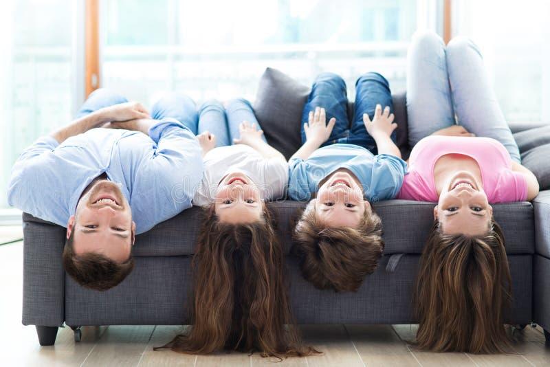 Family lying upside down on sofa stock photography